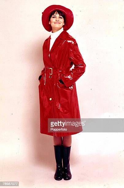 9th January 1965 A portrait of a woman wearing a red plastic raincoat with matching hat whilst smiling with her hands in her pockets at the camera