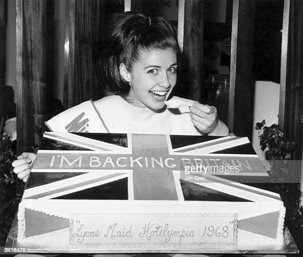 Miss Bournemouth Anita Shannelle tucks into a huge cake decorated with 'I'm Backing Britain' written on a Union Jack at the Lyon's Maid stand...