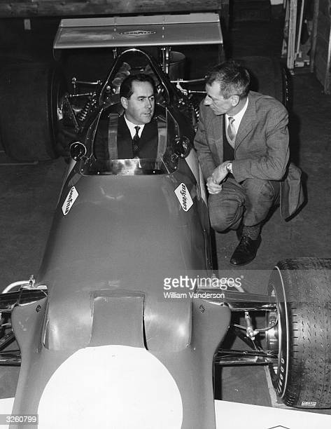 Racing driver and car builder Jack Brabham sits behind the wheel of his new car, the BT 33 Formula One Brabham racing car, talking to the car's...
