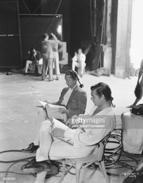 Franchot Tone and Clark Gable peruse their scripts on the set of 'Mutiny on the Bounty' directed by Frank Lloyd