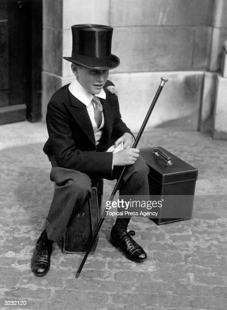 A Harrow schoolboy sits on his suitcase as he waits to set off for a cricket match at Lord's