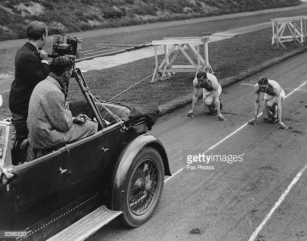 Cameramen filming runners C B Holmes and W Roberts on the race track at Manchester for a documentary on Britain's leading athletes.
