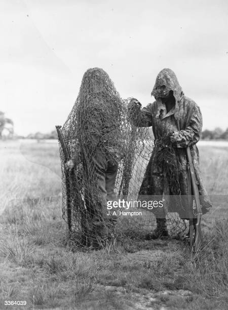 Scout helps his 'observer' into his camouflage gear, ready for a demonstration of how to root out snipers in No Man's Land. In peacetime these men...