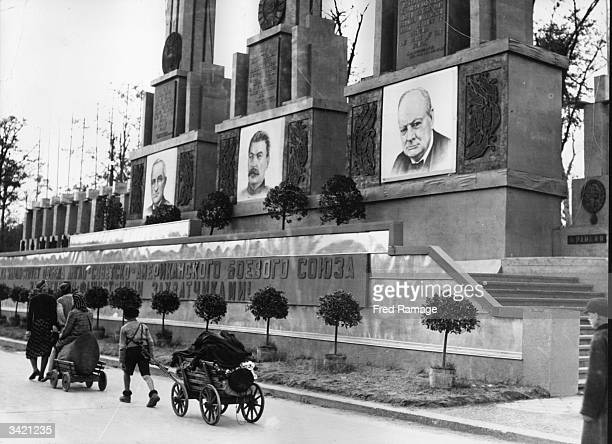 Germans returning to Berlin walk past the saluting base for the Berlin Victory March Past which is decorated with pictures of President Truman Stalin...