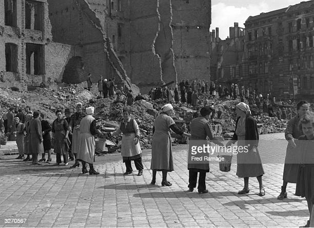 Women in postwar Berlin East Germany form a 'chain gang' to pass pails of rubble to a rubble dump to clear bombed areas in the Russian sector of the...