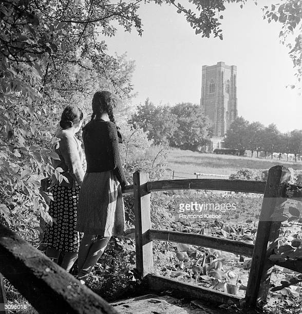 Two young women down by the Fishpond stop and listen to the bells of Lavenham Church in Suffolk Original Publication Picture Post 4827 BellRingers At...