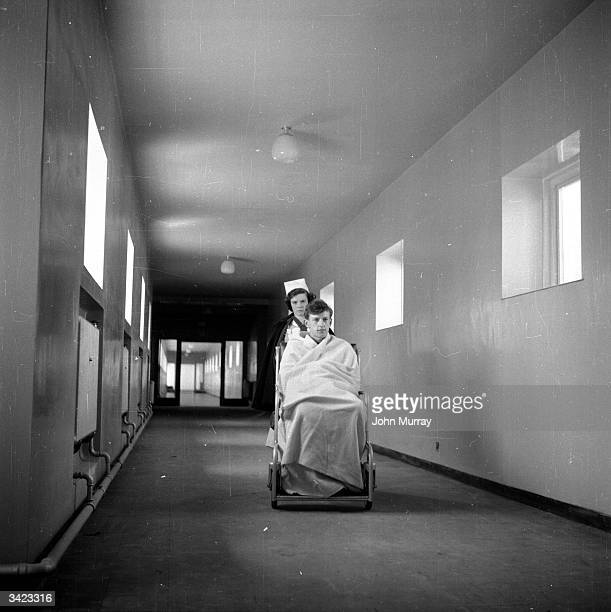 A nurse pushing a wheelchair bound patient down a hospital corridor Original Publication Picture Post 7844 The Hospital Of The Future pub 1955
