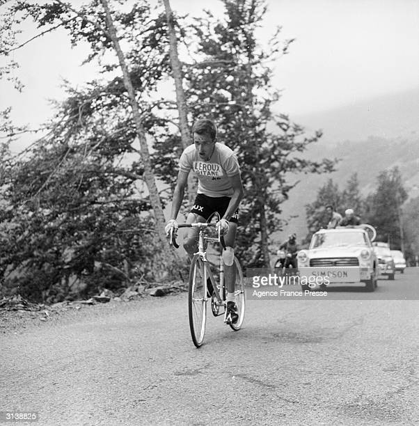 The first Briton to wear the yellow jersey, Tommy Simpson being followed by his support car. He is up with the leaders during the 13th stage of the...