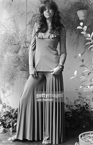 Fulllength portrait of American singer Carly Simon standing among potted and hanging plants wearing a loose pants outfit with a ruffled collar New...
