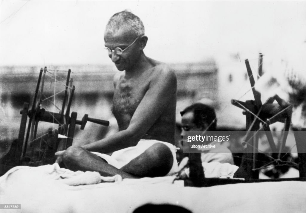 Indian Nationalist leader Mahatma Gandhi (Mohandas Karamchand Gandhi, 1869 - 1948) at a spinning wheel during a 'Charlea' demonstration in Mirzapur, Uttar Pradesh.