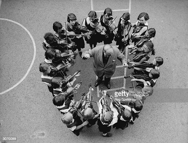 Pupils at Haselrigge Road School Clapham London form a circle round their teacher as they practise the violin for their forthcoming participation in...
