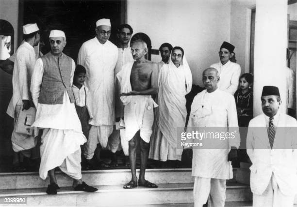 Indian thinker statesman and nationalist leader Mahatma Gandhi centre waiting for a car outside Bifla House Bombay on his return from Rajkoy Amongst...