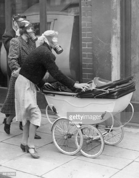 Gas masked young mother attends to her child's pram gas mask during a surprise gas test in Kingston.