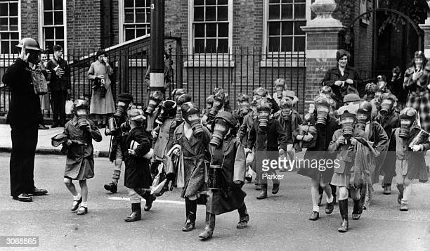 A horde of children wearing gas masks carry out a practice evacuation of a school in Kingston Greater London after a canister of tear gas was...
