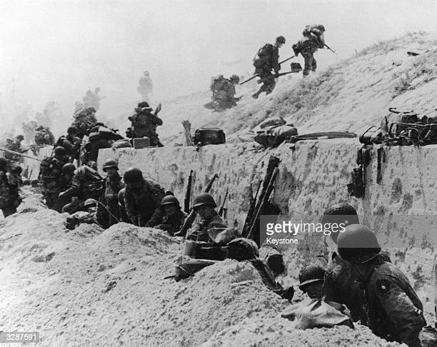 American troops advance over the crest of a concrete sea wall after the successful landings on Utah Beach in Normandy France whilst comrades shelter...