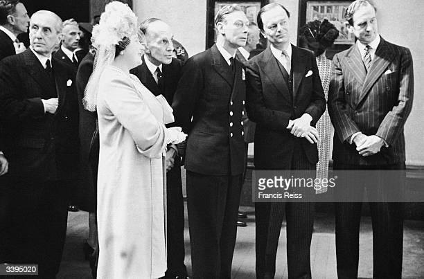 King George VI centre and Queen Elizabeth at the National Gallery London at an exhibition of works which were held in storage during World War II...