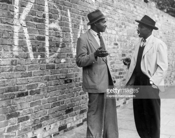 Two Jamaican men talking in a street in Brixton south London The graffiti on the wall stands for 'Keep Britain White'