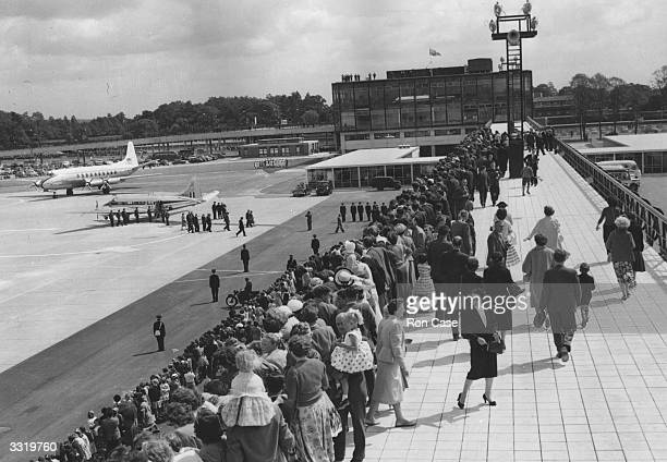 A crowd of people watching the arrival of Queen Elizabeth II and the Duke of Edinburgh for the official opening of Gatwick Airport