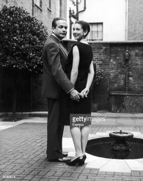 Fulllength image of British ballerina Dame Margot Fonteyn standing outdoors and holding hands with her husband Panamanian diplomat Dr Roberto Arias...