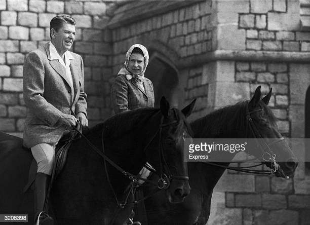 American President Ronald Reagan and Queen Elizabeth II engaged in conversation while horseback riding on the grounds of Windsor Castle, Windsor,...