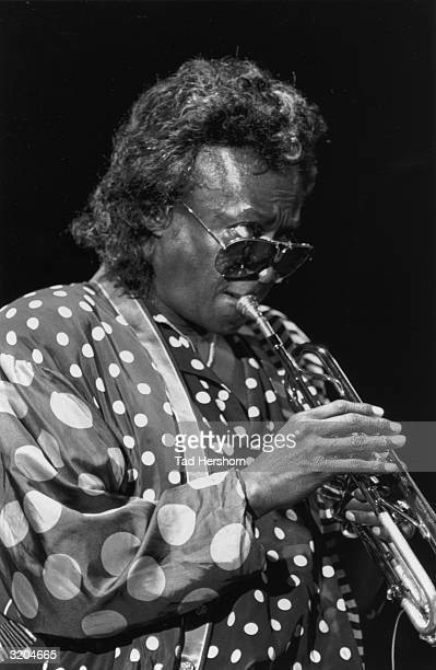 American jazz musician Miles Davis wearing a polka dot outfit and aviator sunglasses plays a trumpet on stage at the JVC Jazz Festival New York City