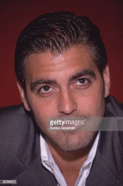 Headshot of American actor George Clooney with stubble in front of a red background