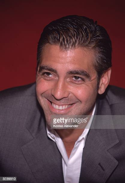 Studio headshot of actor George Clooney smiling and leaning forward in front of a red backdrop