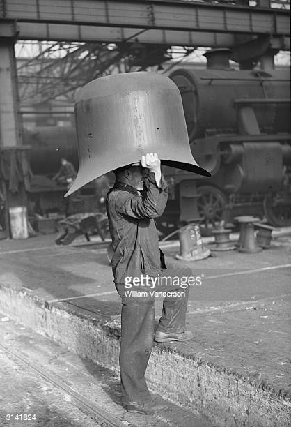 A workman carrying an engine dome at a locomotive works in Crewe