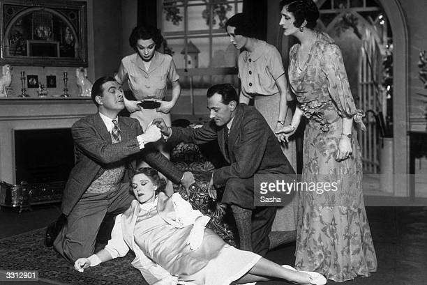 A woman lying in a faint on the floor is surrounded by concerned friends in a scene from the play 'Bats in the Belfry' at the Ambassador's Theatre...
