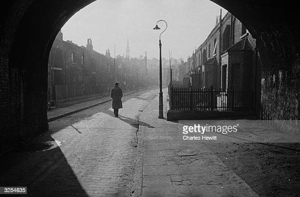 A solitary figure walks down a deserted street in London's East End which London County Council plans to redevelop as part of its postwar rebuilding...