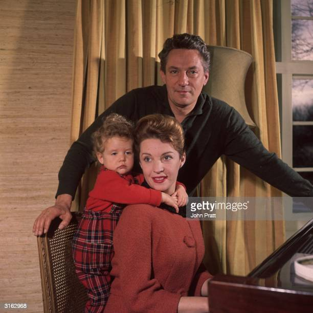 Actor Peter Finch round the piano at his home in Herfordshire with his wife Yvonne and their daughter Samantha