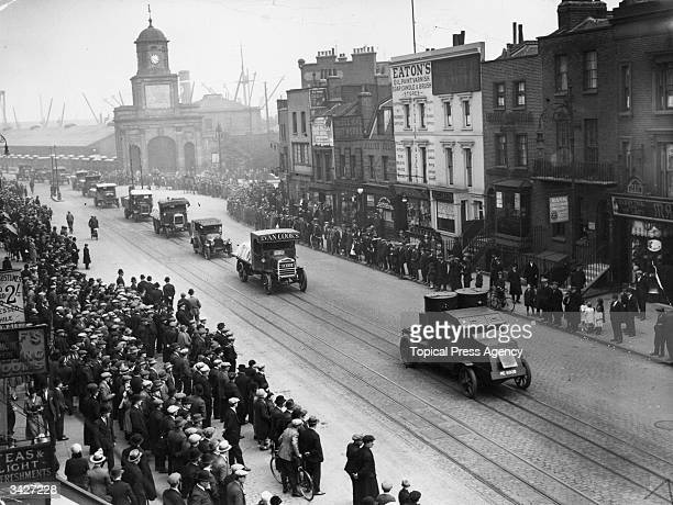 A crowd watches as a food convoy guarded by armoured cars drives down India Dock Road in east London during the 1926 General Strike