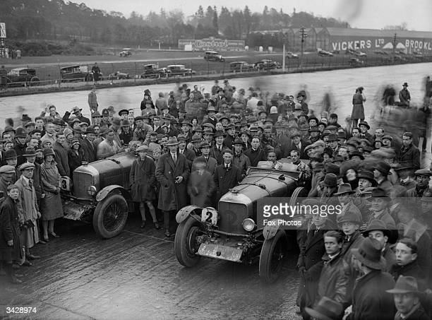 Spectators gather round two of the cars on the second day of a 'Double Twelve' race at Brooklands Weybridge Surrey it was win by Wolf Barnato in a...