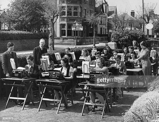 Children of the East London Day Continuation School enjoy their openair typing lesson at Clacton a popular destination for evacuees from London...