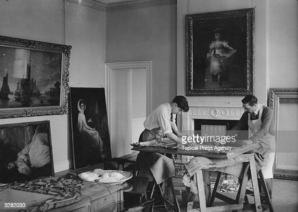 Picture restorers in the library at Kenwood House framing paintings in preparation for the reopening of the stately home on Hampstead Heath for the...