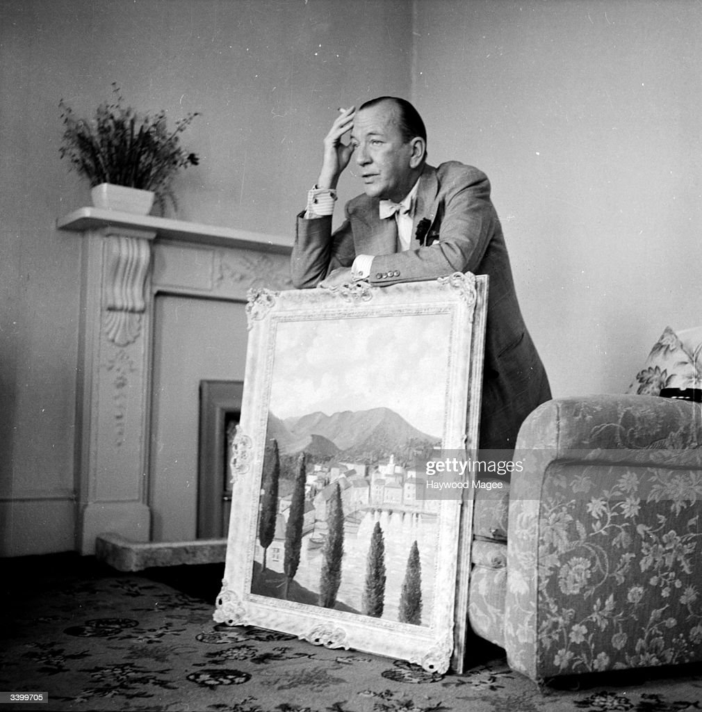 English actor and playwright Sir Noel Coward (1899-1973) with one of his paintings. He and other amateur artists will be exhibiting works at London's Trafford Gallery to raise money for a Toc H charity. Original Publication: Picture Post - 6501 - They Paint For Pleasure - pub. 1953
