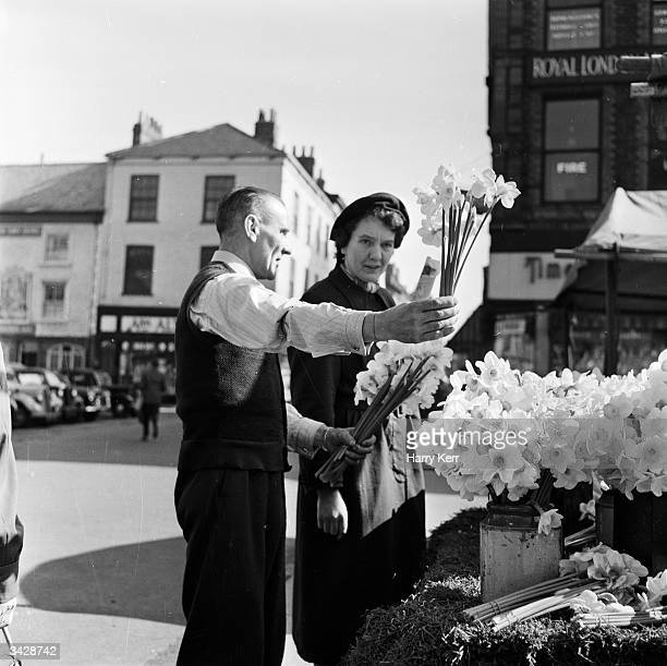 A tourist buys a bunch of daffodils from a street trader in York city North Yorkshire