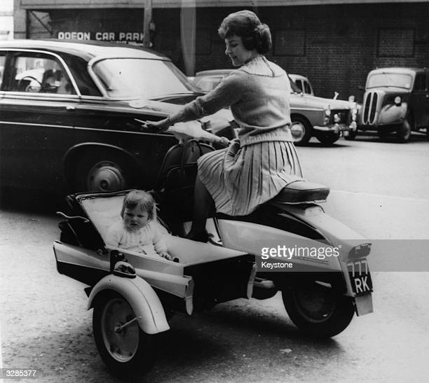 A new design from the makers of Lambretta Scooters Anita White of Teddington rides a powerdriven pram with her daughter Anita
