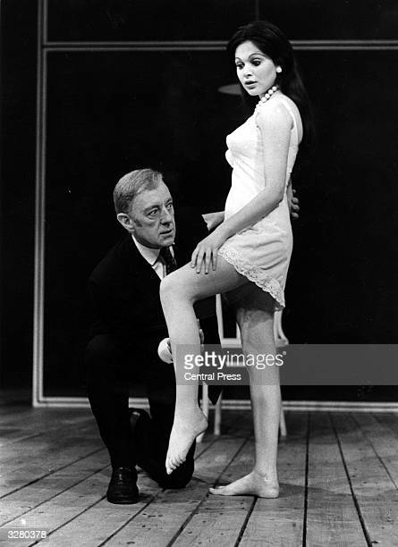 Sir Alec Guinness examines a patient played by Madeleine Smith in the stage play 'Habeas Corpus' by Alan Bennett