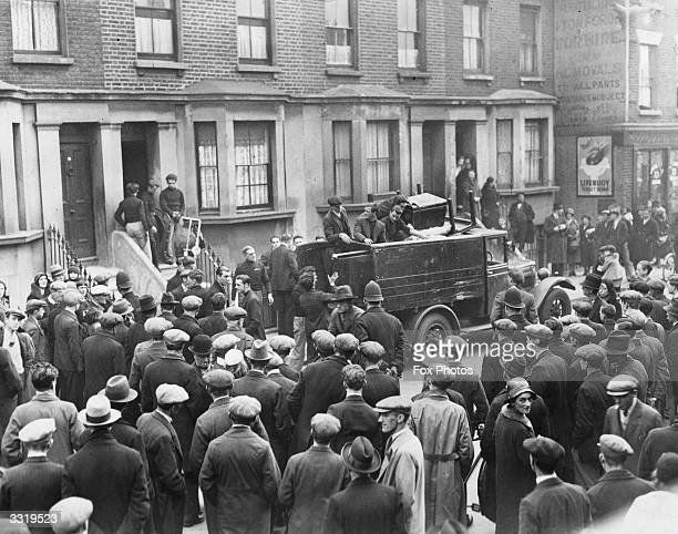Fascists removing furniture from a house at Battersea London watched by a large crowd They are moving the occupants to a new address in Chelsea after...