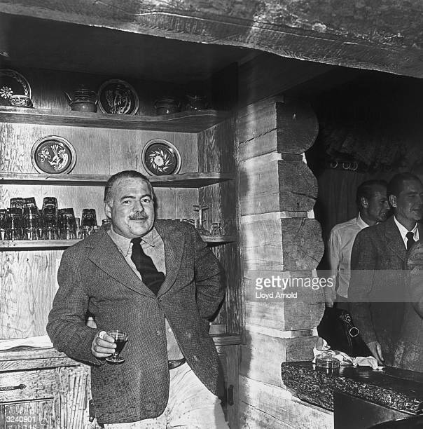 American writer Ernest Hemingway holds a cordial at a party for actor Gary Cooper at Trail Creek Cabin in Ketchum Idaho