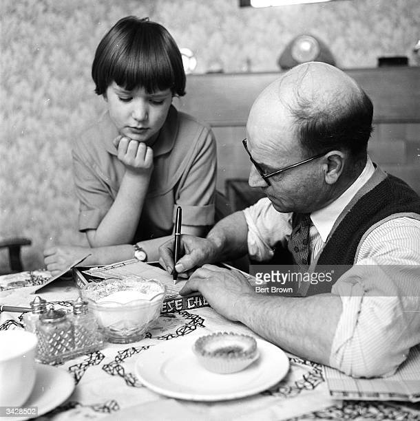 10yearold Bernie watches her father Bernard Bradbury of Hinckley in Leicestershire filling out his pools coupon Mr Bradbury recently won 15000 in the...