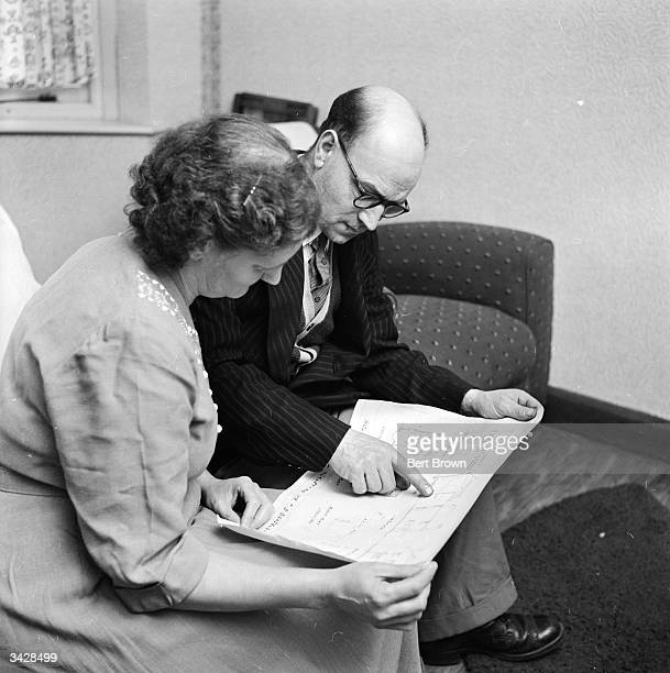 Mr and Mrs Bernard Bradbury of Hinckley in Leicestershire examine architectural plans for their new house Mr Bradbury recently won 15000 in the...