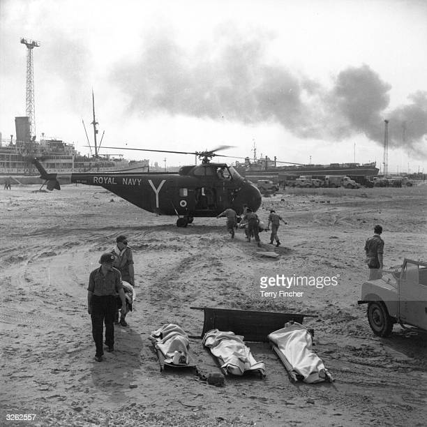 Near the Casino Palace Hotel at Port Said in Suez, stretcher bearers carry Egyptian wounded to the Fleet Air Arm Westland Whirlwind helicopter to...