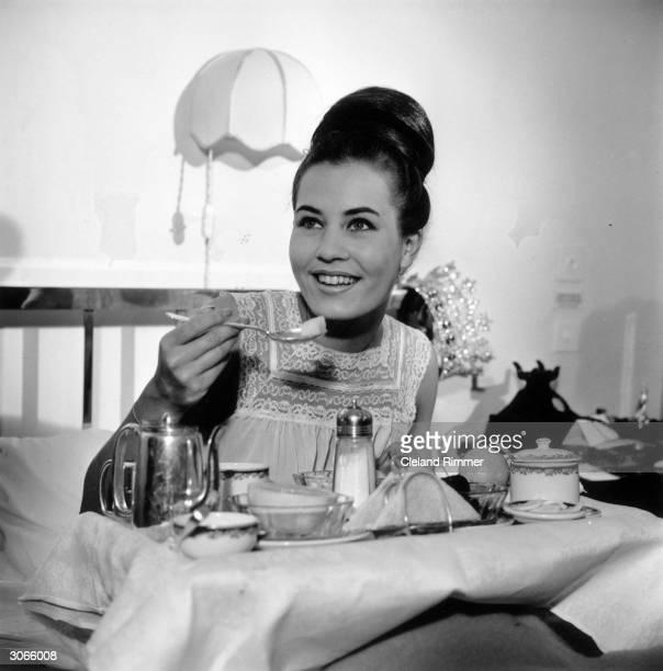 Caterina Lodders, Miss World 1962, enjoys breakfast in bed.
