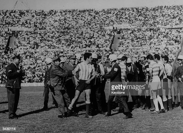 Police lead a Racing Club footballer off the pitch during a bad tempered game against Celtic in the World Club Championship