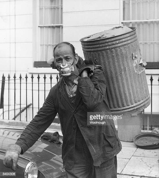 A dustman returning to work in Camden after a six week strike wears a mask to protect him from the rotting rubbish fumes