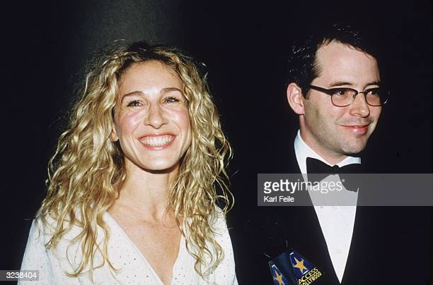 Married American actors Sarah Jessica Parker and Matthew Broderick smiling while standing in front of a handheld 'Access Hollywood' microphone at the...