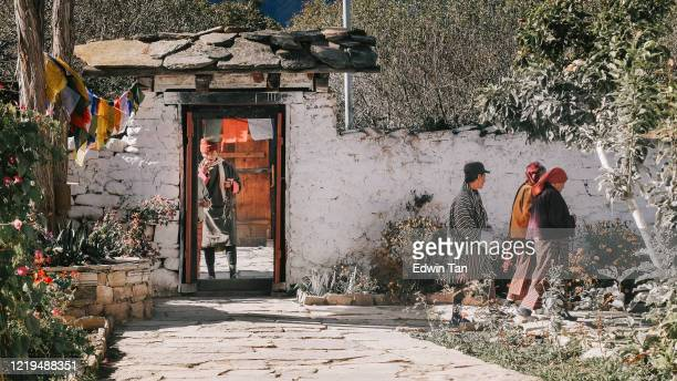 9th november 2017 3 bhutanese villagers walking pass residential buildings village while another villager standing in front of the main doorstep - bhutan stock pictures, royalty-free photos & images