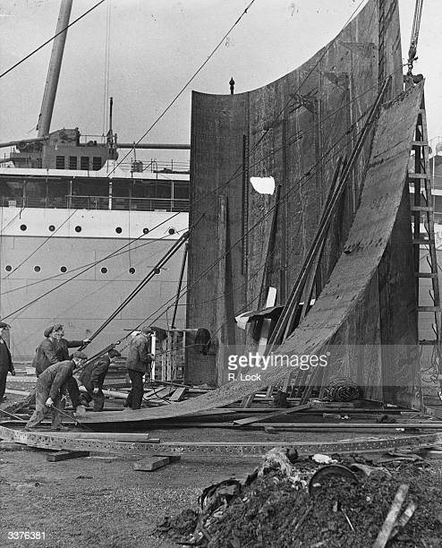 Shipyard workers constructing the funnel for the new liner the 'Stirling Castle' on the quay at Belfast's Harland and Wolff shipyard
